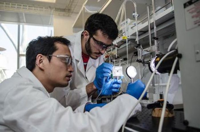 Chengxiang Xiang and Erik Verlage, JCAP team members, assemble part of the artificial leaf.