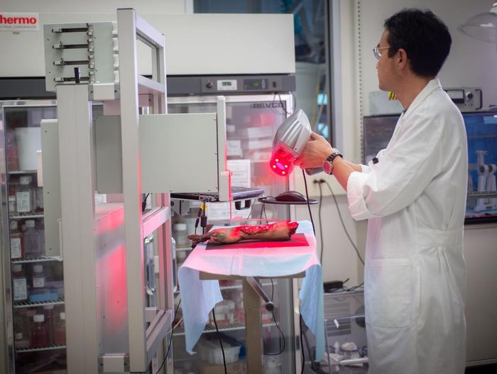 A WFIRM technician operates the mobile bio printer for skin printing on a limb demo./ Credit: WFIRM Photo