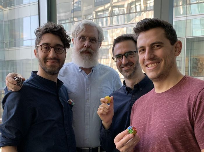 In this photo Sam Sinai, George Church, Eric Kelsic, and Pierce Ogden are holden small models of the AVVs capsid in their hands. / Credit: Wyss Institute at Harvard University