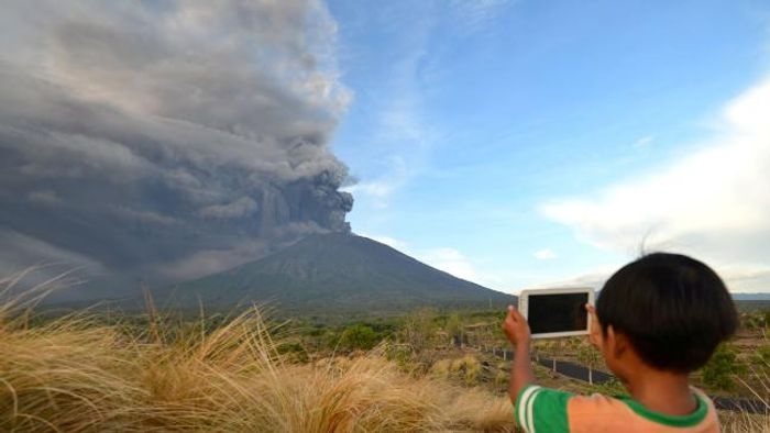 A young boy snaps a shot of the ash coming from Mount Agung. Photo: The Australian