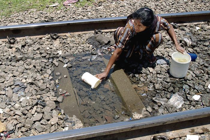 A slum dweller keeps an eye open fro trains as she collects water for drinking from a puddle in between railway tracks in Mumbai. Photo: Reuters