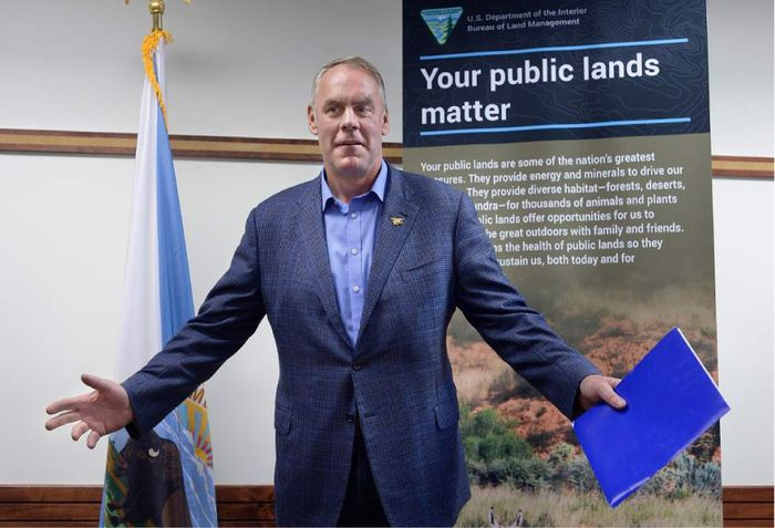 "Interior Secretary Zinke, standing in front of a poster that says ""Your public lands matter"". Photo: Salt Lake City News Archive"