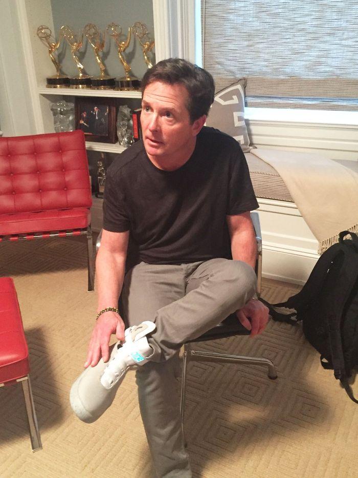 Michael J. Fox puts on a Nike self-lacing shoe.
