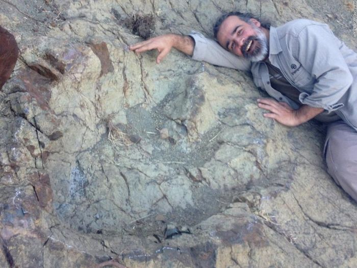 Scientist Sebastian Apesteguia poses for a photo next to the massive footprint.