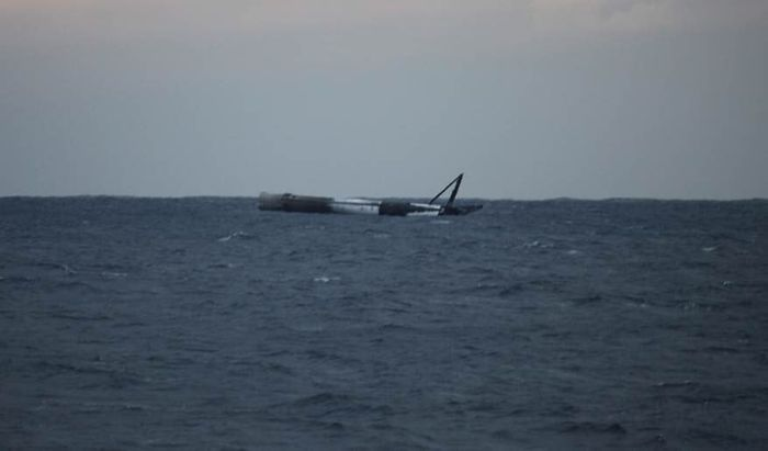 A SpaceX Falcon 9 rocket lays on its side in the Atlantic Ocean after testing a high-powered landing technique.