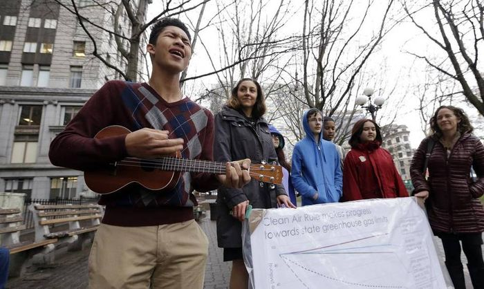 Petitioner Aji Piper, left, starts a news conference with a song as he stands with other children asking a court to force state officials to adopt new rules to limit carbon emissions, Tuesday, Nov. 22, 2016, in Seattle. Elaine Thompson AP