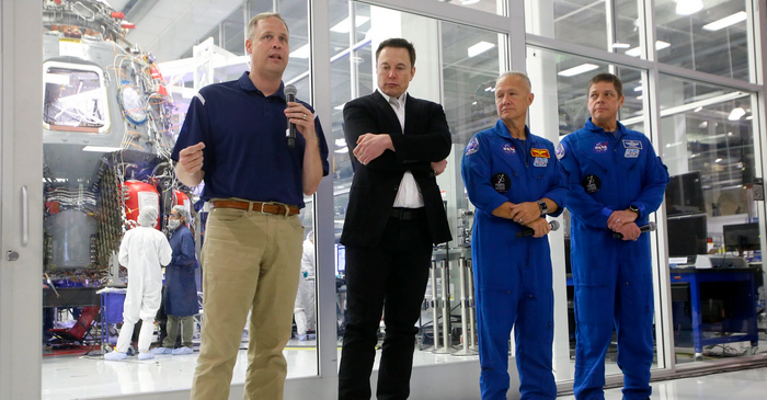 Jim Bridenstine and Elon Musk accompany two Commercial Crew astronauts during a press conference.