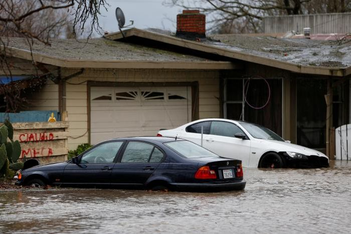 A partially submerged home and vehicles are seen during a winter storm in Petaluma, California, January 8, 2017. REUTERS/Stephen Lam