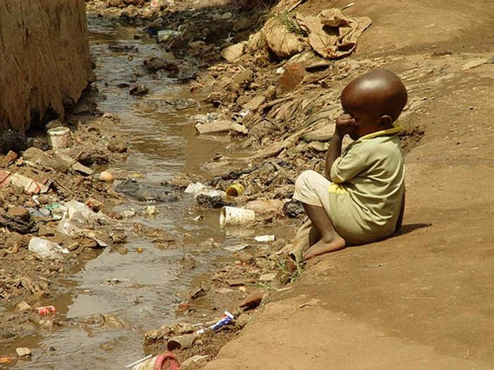 Child next to open sewer in slum in Kampala, Uganda, at risk of diarrhea and stunted growth