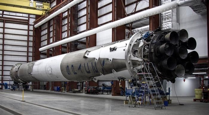 The SpaceX Falcon 9 reusable rocket that blasted off last month sits sideaways in a hangar.