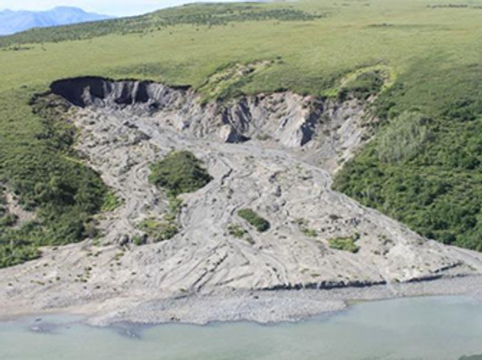 A retrogressive thaw slump where the top layer of usually frozen soil has melted and slid into the river below. / Credit: NPS Photo.