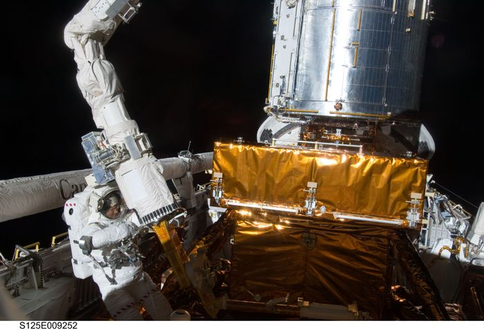 Image of Astronaut Michael Good making repairs on the Hubble Space Telescope in 2009
