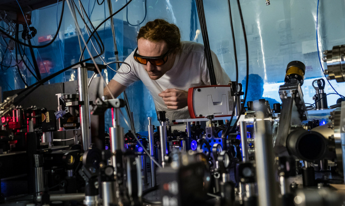 Rice physicist Joe Whalen and his laser cooling system. Credit: Jeff Fitlow/Rice University