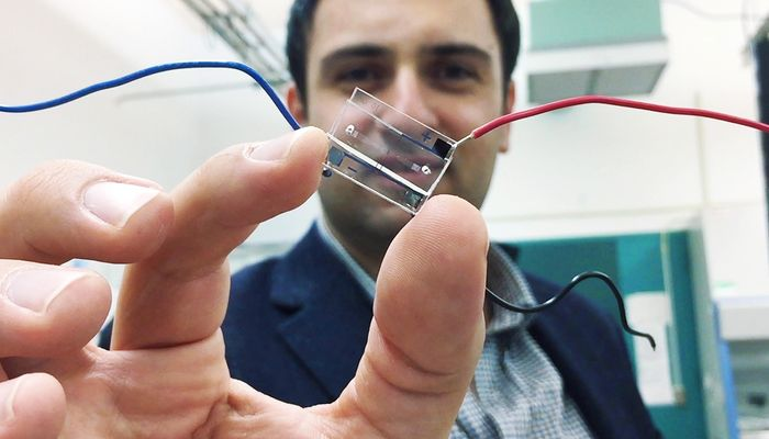 Fatih Sarioglu holds a hybrid microfluidic chip that uses a simple circuit pattern to assign a unique seven-bit digital identification number to each cell passing through the channels.