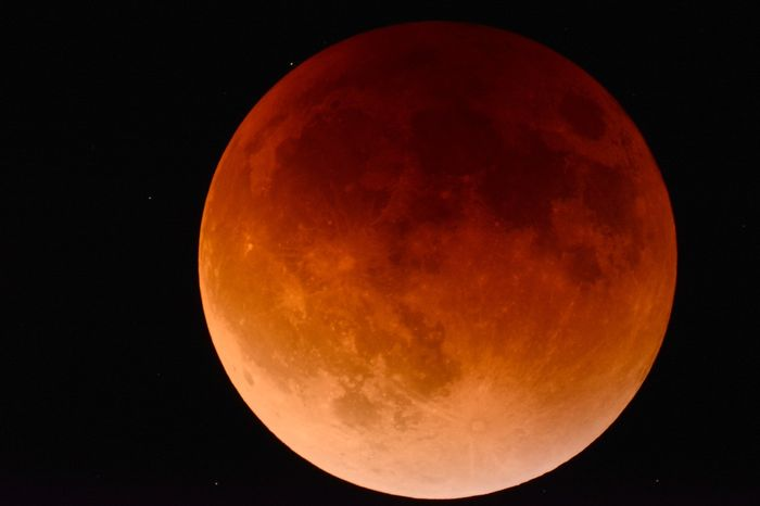 This picture depicts a Blood Moon, which happens when the Earth blocks the Sun's light from reaching the lunar surface.