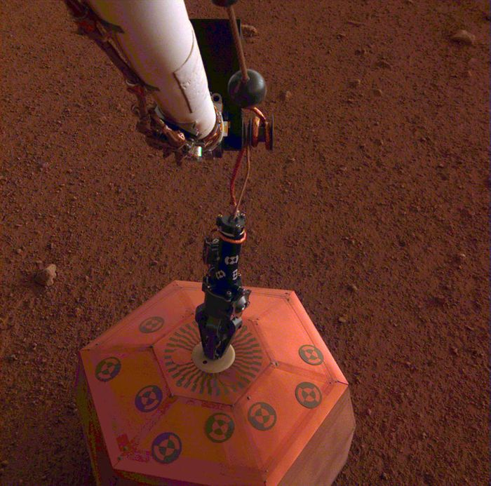 A picture of InSight's SEIS instrument in the soil beside the lander.