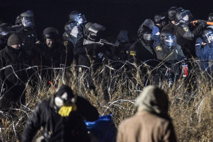 Police confront protesters with a rubber bullet gun during a protest at Standing Rock. Photo: PBS
