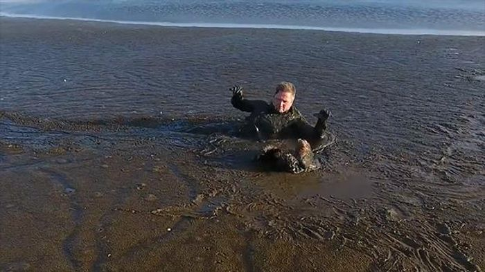 A photographer drags himself through a pit of thick mud to rescue a stuck white-tailed eagle.